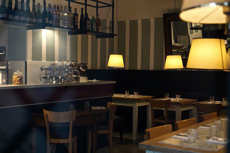 interno ristorante con luci soffuse e tavoli in legno