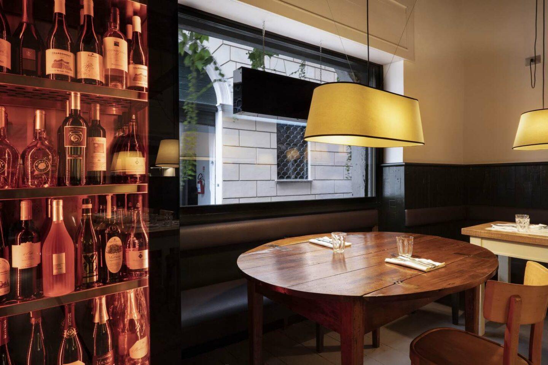 interno ristorante con tavoli di legno e cantina vini