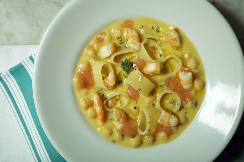 minestra con ceci e gamberi in piatto fondo bianco