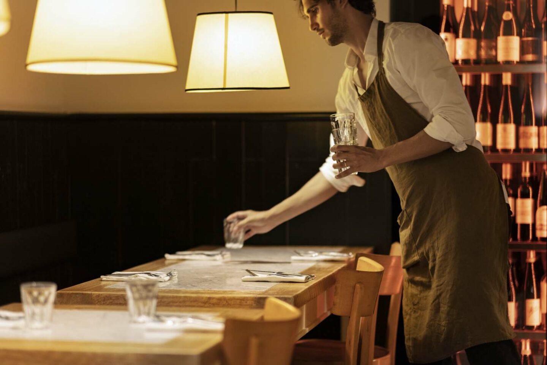 cameriere con grembiule marrone e camicia bianca apparecchia la tavola