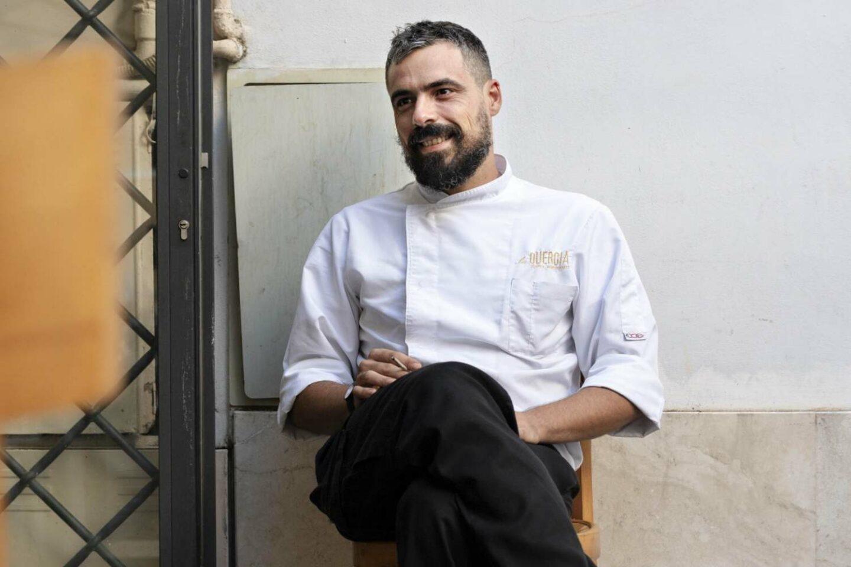 chef marco gallotta con giacca da chef bianca e pantaloni neri seduto fuori il ristorante