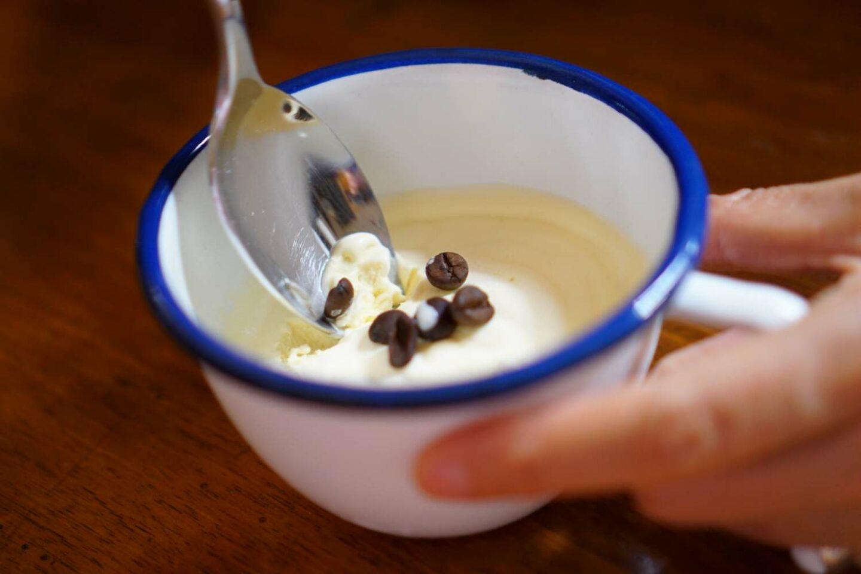 tazza bianca con bordo blu con dentro crema e chicchi di caffè
