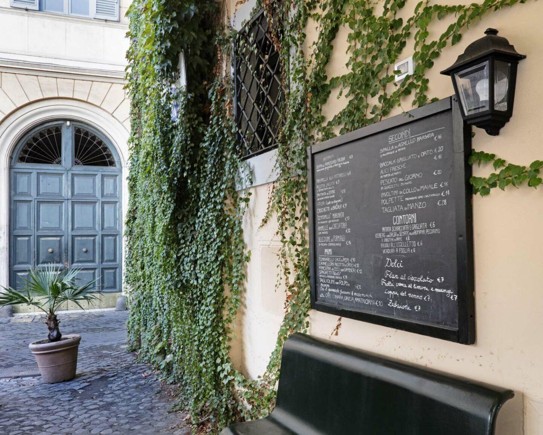 dehors ristorante con lavagna nera con menu e edera sul muro
