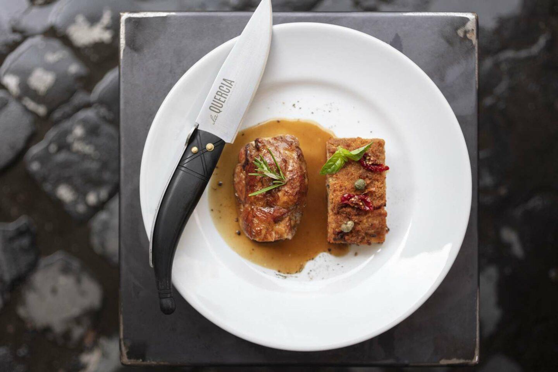 piatto bianco con due filetti di carne e coltello con logo la quercia