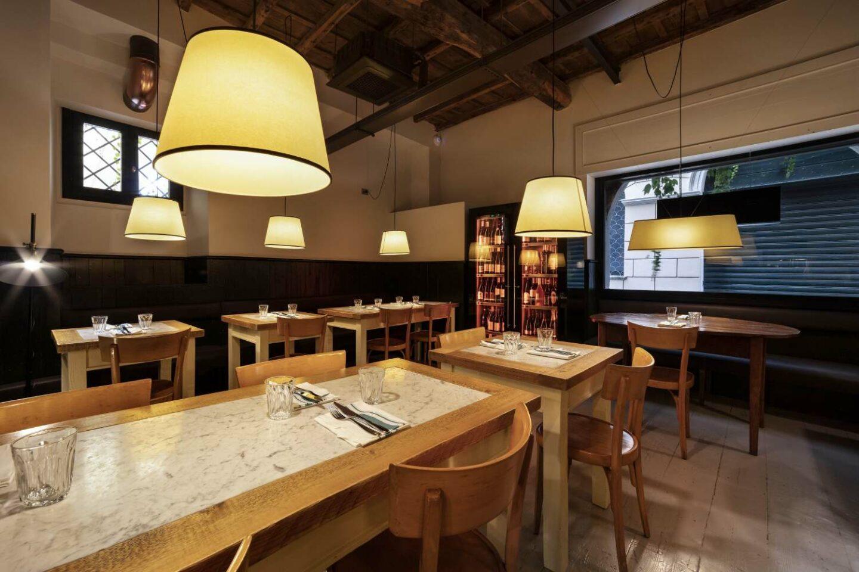 tavoli in legno e marmo con lampade sospese accese