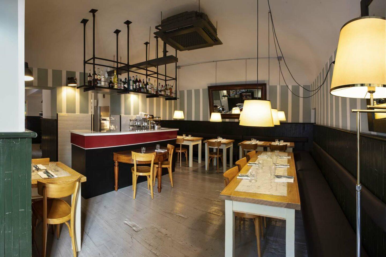 entrata ristorante con tavoli in legno e bancone e lampade