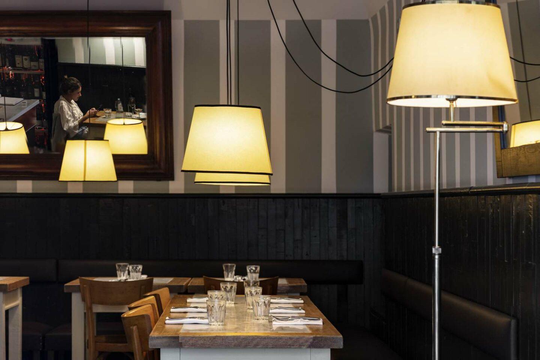 sala interna del ristorante con tavoli in legno apparecchiati e lampade accese