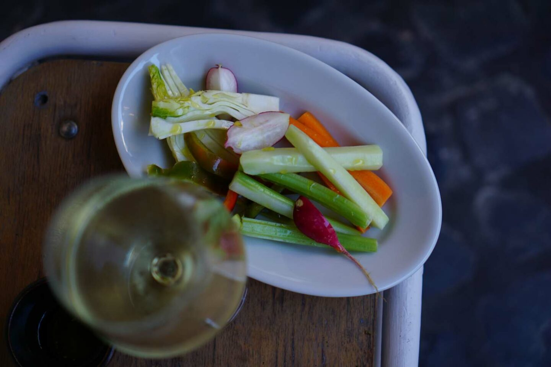 pinzimonio in piatto bianco e calice di vino bianco