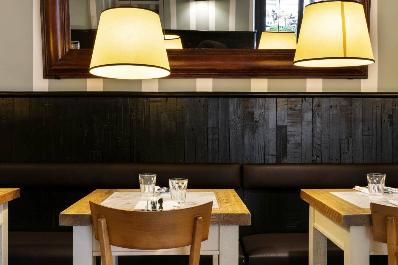 2 tavoli di legno e marmo apparechiati, specchio e 2 lampade accese