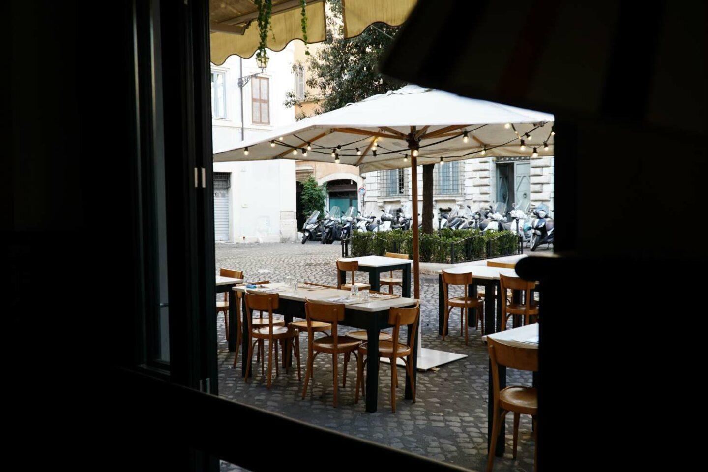 sala esterna vista dall'interno: tavoli di legno apparecchiati, gazebo con tenda bianca e lucine accese