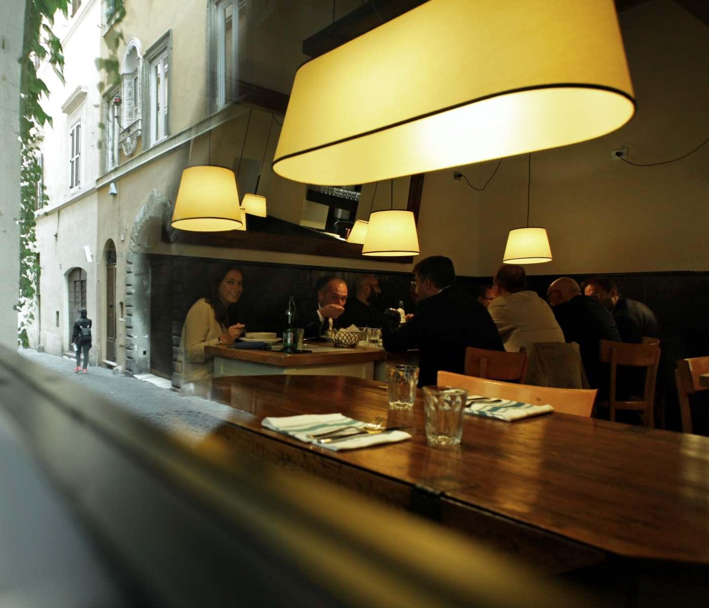 tavoli interni con clienti che mangiano seduti, visti dall'esterno del locale